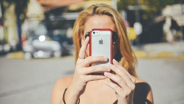 Una chica con un teléfono móvil iPhone de Apple - Sputnik Mundo