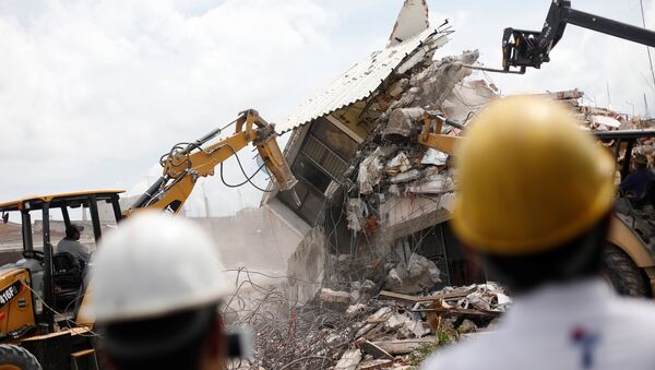 Excavadores derruyen una casa devastada por el terremoto del 19 de septiembre en Jojutla de Juárez, México - Sputnik Mundo