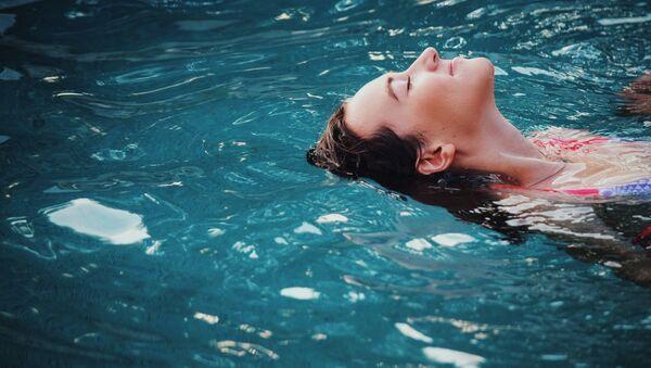 Una joven en una piscina - Sputnik Mundo