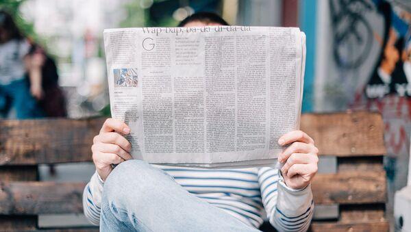 Una persona lee un periódico - Sputnik Mundo