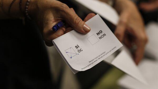 Una mujer muestra su boleta con la casilla Sí marcada en la Escuela Concepcio de Barcelona el 1 de octubre de 2017 - Sputnik Mundo