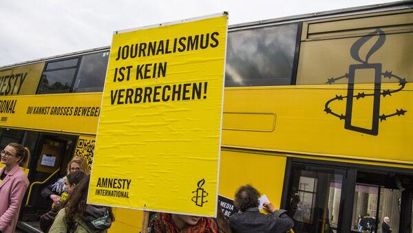 Una activista de Amnistía Internacional con un cartel: Periodismo no es crimen - Sputnik Mundo