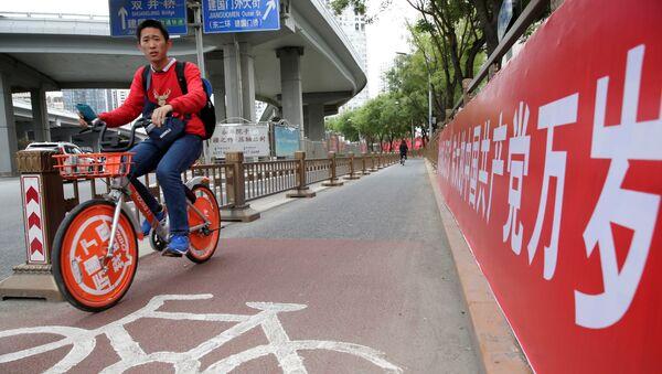 Un ciclista chino cerca del cartel que dice Que viva el gran partido Comunista de China - Sputnik Mundo