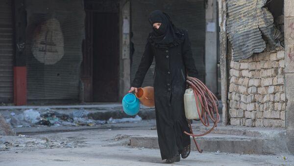 Una mujer camina en una zona residencial de una ciudad siria (imagen referencial) - Sputnik Mundo