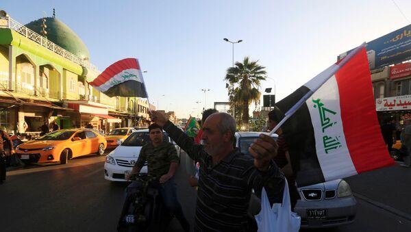 Un hombre vende banderas de Irak en Kirkuk - Sputnik Mundo