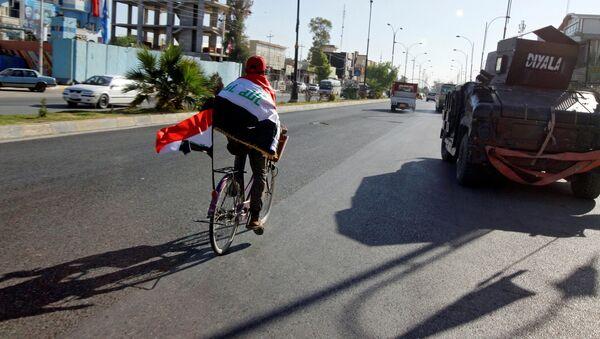 Un hombre con las banderas de Irak en la ciudad de Kirkuk - Sputnik Mundo