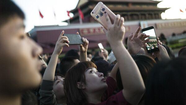Una joven china sacando una foto con un teléfono móvil en Pekín - Sputnik Mundo