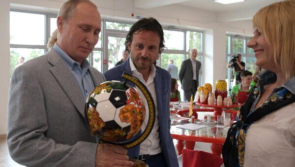 El presidente Vladímir Putin con el globo futbolero con jojlomá - Sputnik Mundo