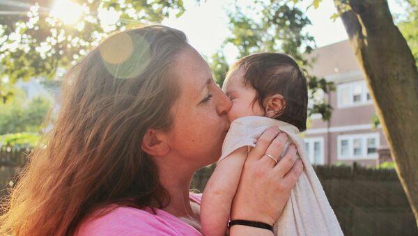 Madre besa a su bebé - Sputnik Mundo