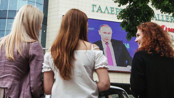 Unas jóvenes rusas están viendo un discurdo del presidente de Rusia, Vladímir Putin, por la televisión - Sputnik Mundo