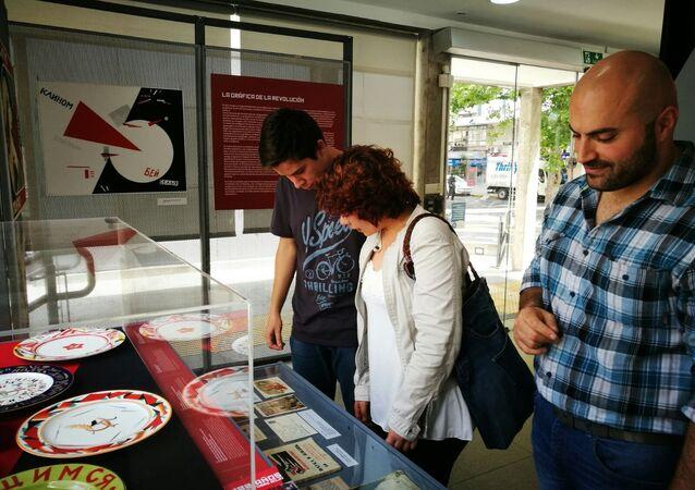 Personas observan la porcelana expuesta en la muestra '100 años de Octubre Rojo', en Montevideo, Uruguay.