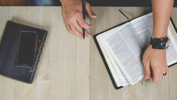 Un hombre de negocio con una Biblia (imagen referencial) - Sputnik Mundo