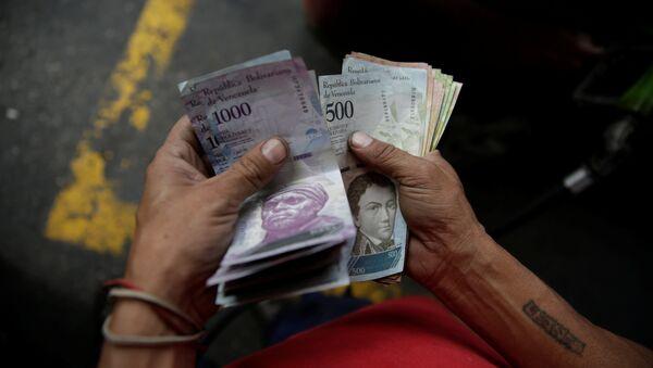Un trabajador cuenta bolívares venezolanos en una gasolinera de la petrolera estatal venezolana PDVSA en Caracas - Sputnik Mundo