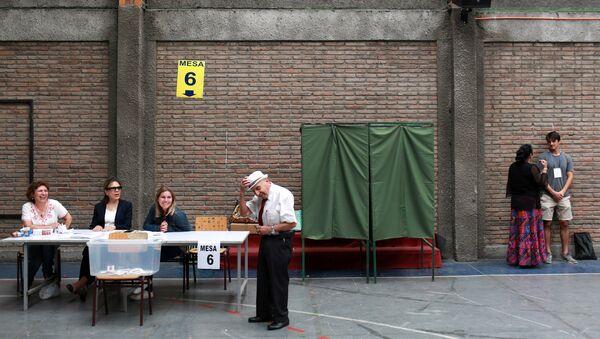 Un hombre votando durante las elecciones presidenciales en Chile - Sputnik Mundo