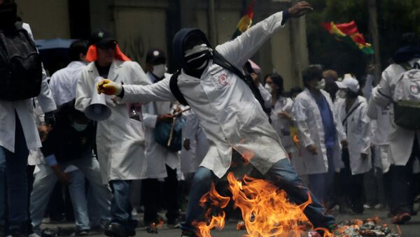 A demonstrator is seen during clashes with riot police as healthcare employees and students refuse new government policies about health system in La Paz, Bolivia - Sputnik Mundo