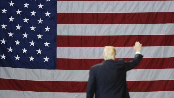 El presidente de EEUU, Donald Trump, con la bandera del país al fondo (archivo) - Sputnik Mundo