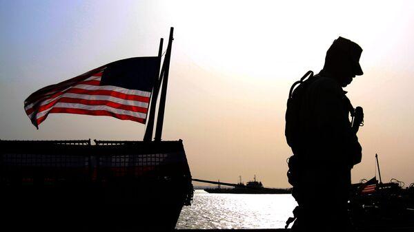 Un soldado de EEUU junto a la bandera estadounidense (archivo) - Sputnik Mundo