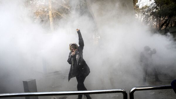 FILE - In this Saturday, Dec. 30, 2017 file photo taken by an individual not employed by the Associated Press and obtained by the AP outside Iran, a university student attends a protest inside Tehran University while a smoke grenade is thrown by anti-riot Iranian police, in Tehran, Iran - Sputnik Mundo