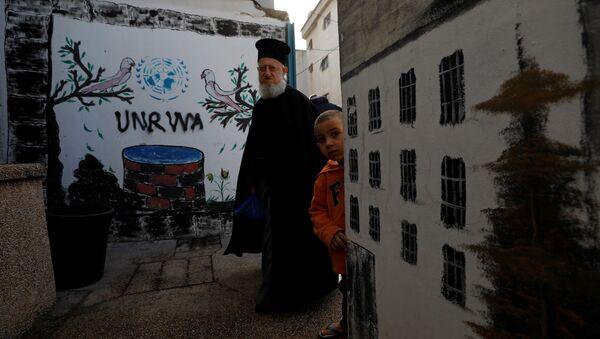 Logo de UNRWA en un campo de refugiados palestinos - Sputnik Mundo