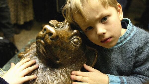 Un niño al lado de la estatua del perro Málchik en el metro de Moscú - Sputnik Mundo