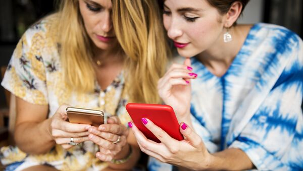 Dos mujeres con teléfonos móviles (imagen referencial) - Sputnik Mundo