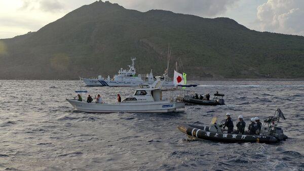 Unos barcos de la Guardia Costera japonesa navegan junto al bote pesquero de los activistas japoneses advirtiendo a los activistas que se alejen de un grupo de islas en disputa llamado Diaoyu por China y Senkaku por Japón - Sputnik Mundo