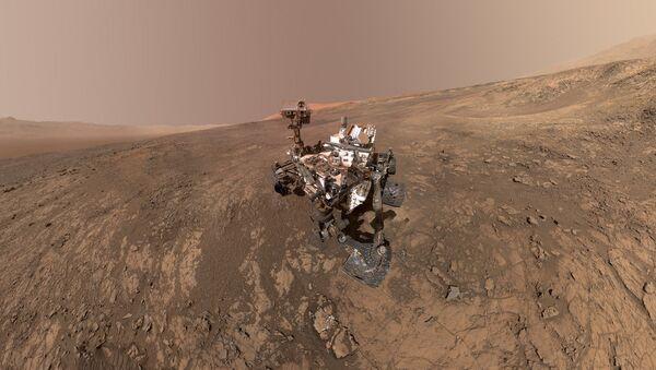 Este autorretrato del rover Curiosity de la NASA muestra el vehículo en la cresta Vera Rubin. Justo detrás del rover empieza una pendiente arcillosa que los científicos están ansiosos por comenzar a explorar. En la próxima semana, Curiosity comenzará a subir esta cuesta. - Sputnik Mundo