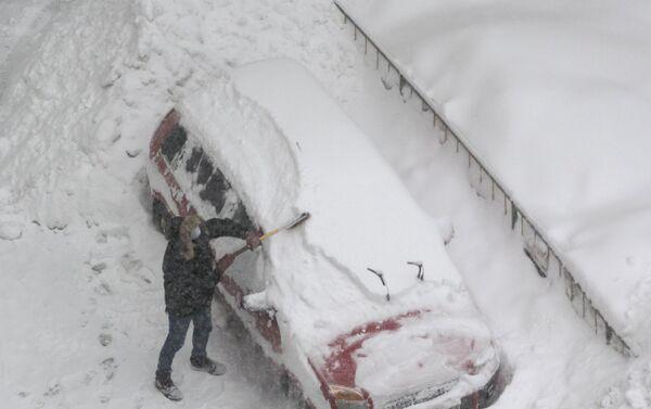 Un hombre está limpiado su auto de la nieve en Moscú - Sputnik Mundo