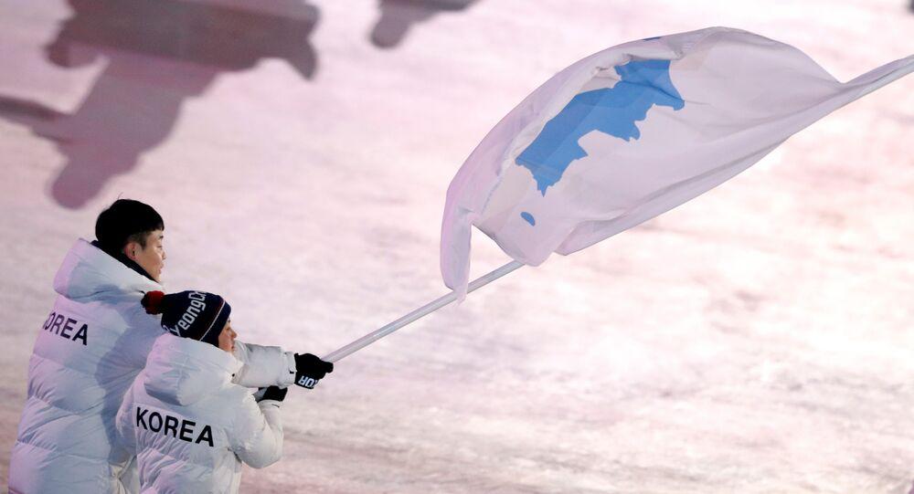Los deportistas con la bandera de la península de Corea