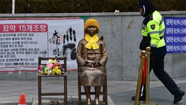 Un policía surcoreano pasa por delante de la estatua de una joven con un vestido tradicional representando a las 'mujeres de consuelo' que sirvieron como esclavas sexuales durante la II Guerra Mundial. - Sputnik Mundo