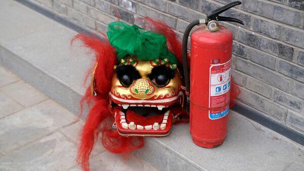 Una máscara de león y un extintor de incendios en Pekín, China - Sputnik Mundo