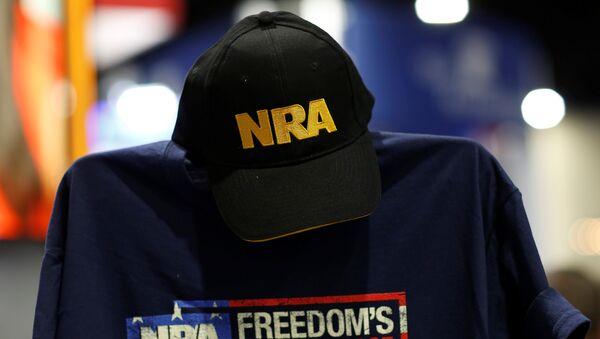 Una gorra y una camisa en el stand de la Asociación Nacional del Rifle (NRA) - Sputnik Mundo