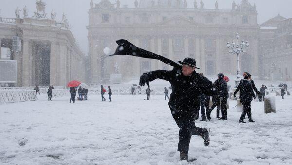 Un cura lanza una bola de nieve en la Plaza de San Pedro, en el Vaticano - Sputnik Mundo