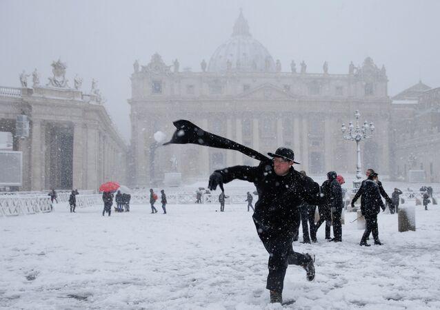 Un cura lanza una bola de nieve en la Plaza de San Pedro, en el Vaticano