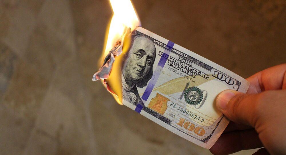 Billete de dólar estadounidense en llamas (imagen referencial)
