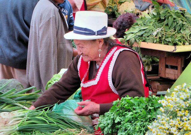 Mujer rural vende en un mercado en Ecuador