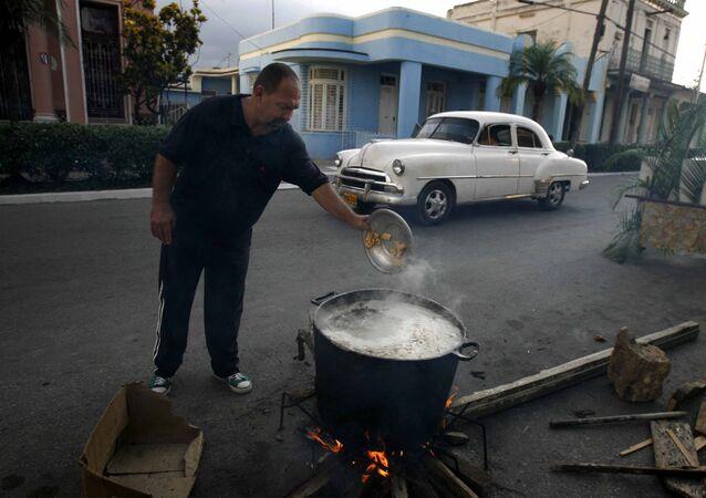 Un hombre prepara caldosa en la calle por el Aniversario de los CDR en Cuba