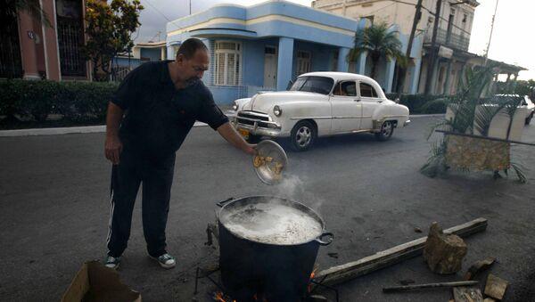 Un hombre prepara caldosa en la calle por el Aniversario de los CDR en Cuba - Sputnik Mundo