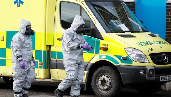 Soldados con trajes de protección caminan al lado de una ambulancia, imagen referencial - Sputnik Mundo