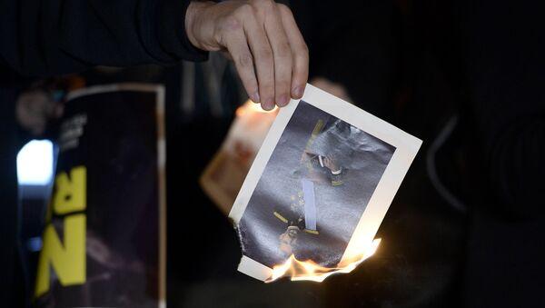 Un manifestante quema una foto del Rey de España, Felipe VI (archivo) - Sputnik Mundo