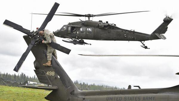 El helicóptero UH-60 Black Hawk y un militar estadounidense - Sputnik Mundo