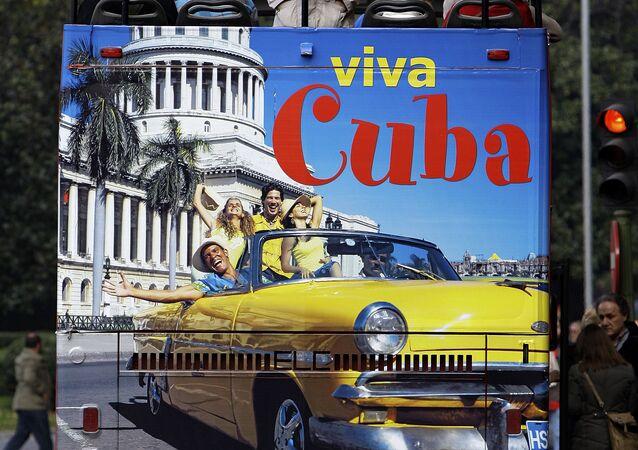 Un hombre en España sobre un bus de turismo que promociona el destino Cuba
