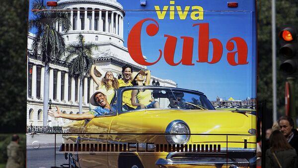 Un hombre en España sobre un bus de turismo que promociona el destino Cuba - Sputnik Mundo
