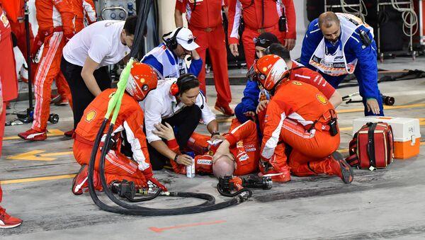 Un mecánico de Ferrari es atendido por sus compañeros después de un accidente durante durante el Gran Premio de Bahréin de F1 - Sputnik Mundo