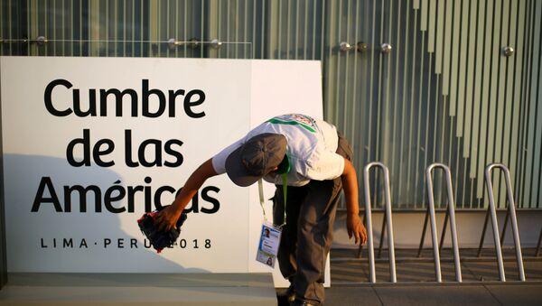 Una mujer limpia un cartel en la previa de la VIII Cumbre de las Américas en Lima, Perú. - Sputnik Mundo