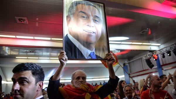 Un hombre con el retrato de Milo Dukanovic, líder del gobernante Partido Demócrata - Sputnik Mundo