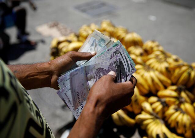 Un vendedor cuenta bolívares en Venezuela