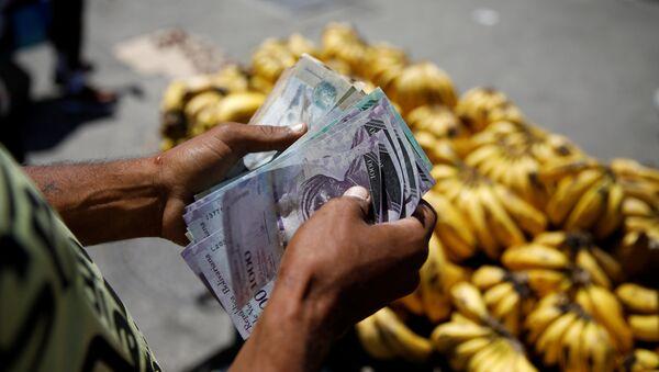 Un vendedor cuenta bolívares en Venezuela - Sputnik Mundo
