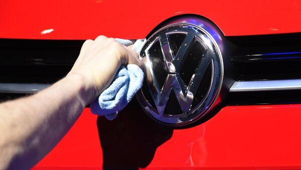 Un hombre puliendo el logotipo del automóvil del fabricante de automóviles alemán Volkswagen - Sputnik Mundo