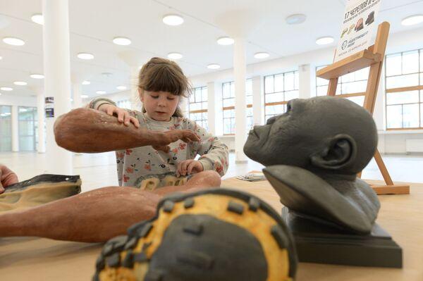 Юная участница фестиваля День недостающего звена знакомится с реконструкцией руки древнего человека Homo naledi - Sputnik Mundo